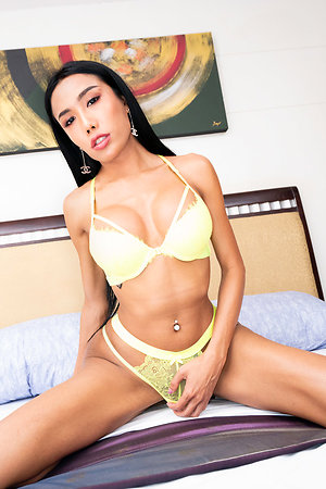 Ladyboy Mos is debilitating a yellow bra added to panty set that changeability well contrast the brush tanned body.
