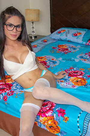 Slim, hard-bodied ladyboy Deni is wearing a titillating white climax thither their way chubby round tits popping out, downcast and white panties, white stockings, and sombre framed glasses.